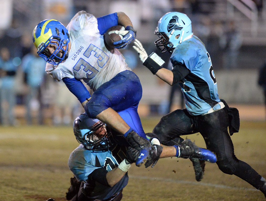 Description of . San Dimas running back Fausto Martinez (#33) is triped up by an Arroyo defender in their CIF Semi-Final football game at Arroyo High School in El Monte on Friday November 22, 2013. (San gabriel Valley Tribune/Staff Photo by Keith Durflinger)