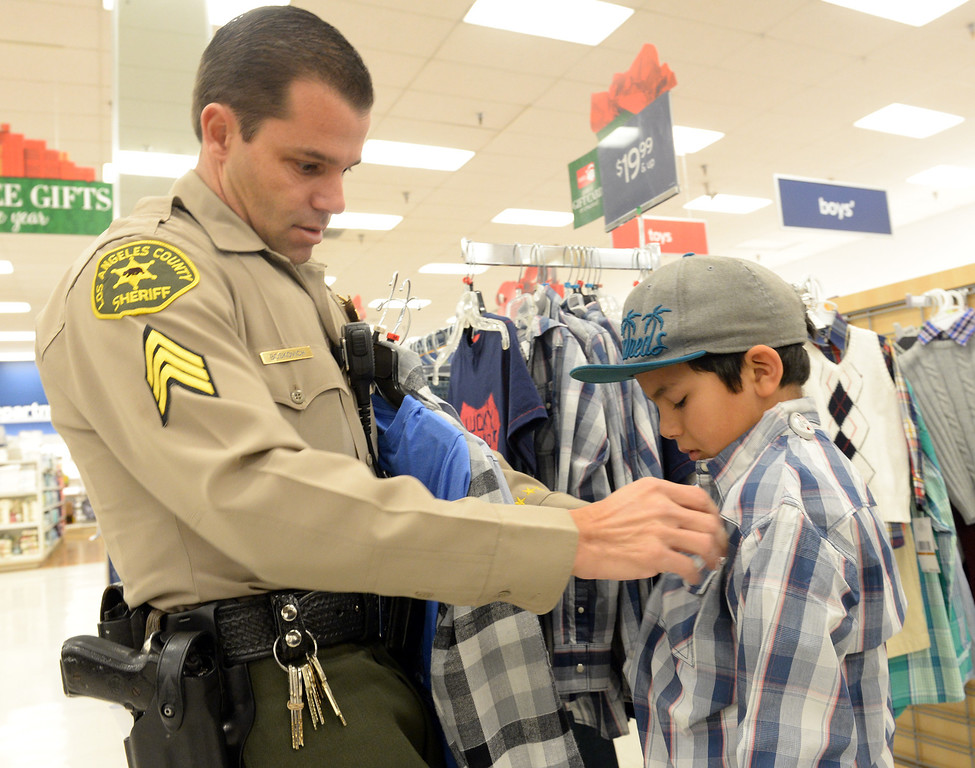 Description of . Los Angeles County Sheriff's Sgt. Marc Boskovich helps Zachary Arreola, 9, try on a shirt during the Rotary Club of La Mirada Christmas Shopping Spree at Marshalls in La Mirada on Wednesday December 11, 2013. Each child is allowed $75 tp spend on clothing and shoes.  (Staff Photo by Keith Durflinger/San Gabriel Valley Tribune)