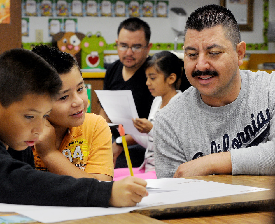 Description of . John Talavera, Benjamin Huzar, with his father Mario Huizar, right,working on school lesson at Elwin Elementary School in Baldwin Park. Elwin Elementary hosted,
