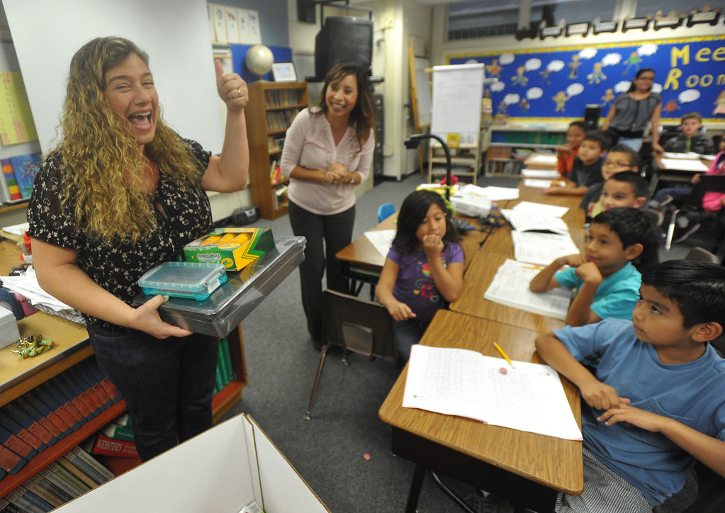Description of . OfficeMax representatives surprise second grade teacher Natalia Weberg, left, with $1,200 worth of classroom supplies and resources at Ceres Elementary School in Whittier on Wednesday October 2, 2013. Principal Julie Gonzalez nominated the second grade teacher for the Adopt a Classroom grant sponsored by Office Max and Adopt a Classroom. (Whittier Daily News/Staff Photo by Keith Durflinger)