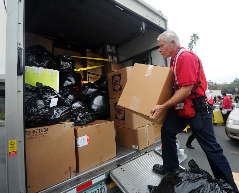 Description of . Heinrich Keifer, a volunteer for American Red Cross, loading truck with clothing, canned goods, toiletries and non-perishable food at the Rose Bowl.  Philippine Typhoon Relief PCC along with Vice Mayor Jacque Robinson, the American Red Cross, Filipino American Television, Victory Cargo, and the PNB-Remittance Centers  sponsoring a Philippine Typhoon Relief Donation Drive Donation Drive Drop-Off Rally Wednesday, November 20, 2013. (Photo by Walt Mancini/Pasadena Star-News)
