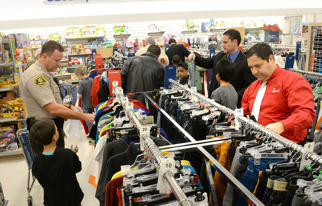 Description of . Volunteers help children shop for clothing during the Rotary Club of La Mirada Christmas Shopping Spree at Marshalls in La Mirada on Wednesday December 11, 2013. Each child is allowed $75 tp spend on clothing and shoes.  (Staff Photo by Keith Durflinger/San Gabriel Valley Tribune)