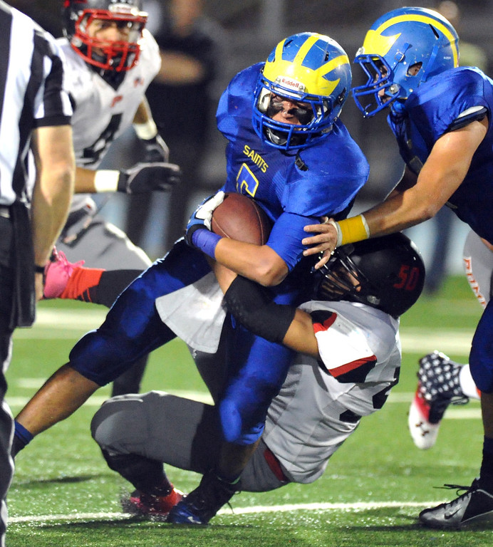 Description of . San Dimas running back Fausto Martinez (#5) is brought down by a Pomona defender in their Valley Vista League football game at San Dimas High School on November 8, 2013. San Dimas defeated Pomona 49-6. (San Gabriel Valley Tribune/Staff Photo by Keith Durflinger)
