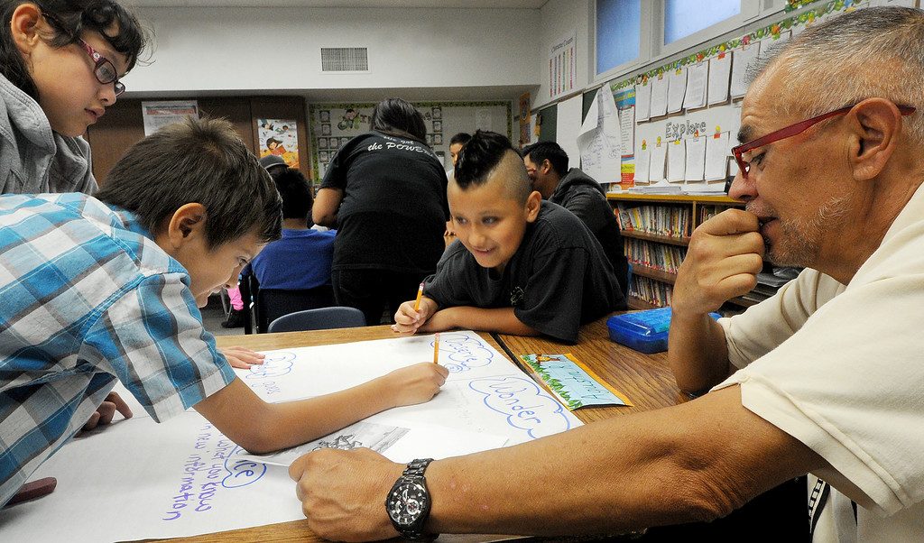 Description of . Elizabeth Soto Angel Reyna, Augstin Rizo, receiving guidance on lesson from Angel Reyna Reyna father Zeferino Reyna at Elwin Elementary School in Baldwin Park host,