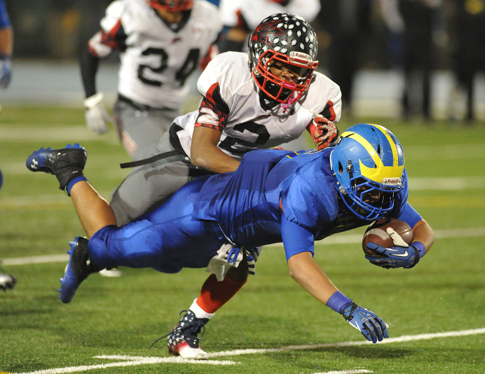Description of . San Dimas running back Fausto Martinez (#5) is brought down by Pomona's Shawn Wilson (#2) in their Valley Vista League football game at San Dimas High School on November 8, 2013. San Dimas defeated Pomona 49-6. (San Gabriel Valley Tribune/Staff Photo by Keith Durflinger)