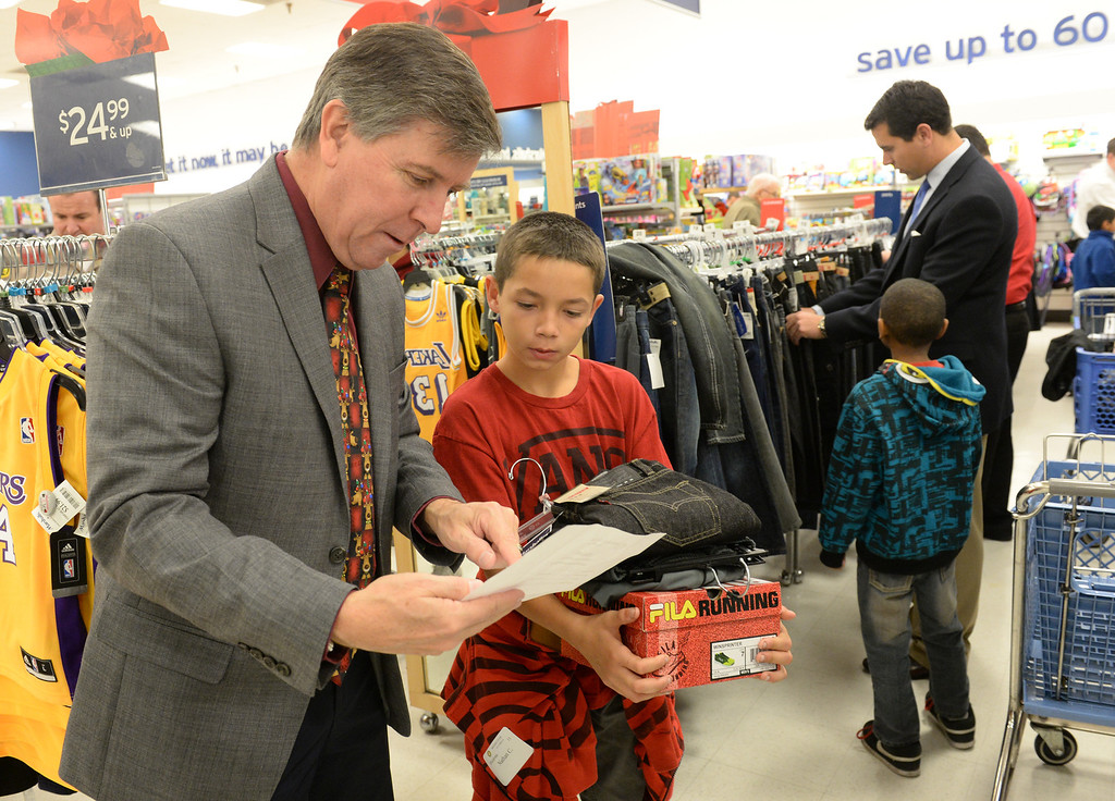 Description of . Phillip Bracey goes through their shopping list with Nathan Cardenas, 11, during the Rotary Club of La Mirada Christmas Shopping Spree at Marshalls in La Mirada on Wednesday December 11, 2013. Each child is allowed $75 tp spend on clothing and shoes.  (Staff Photo by Keith Durflinger/San Gabriel Valley Tribune)