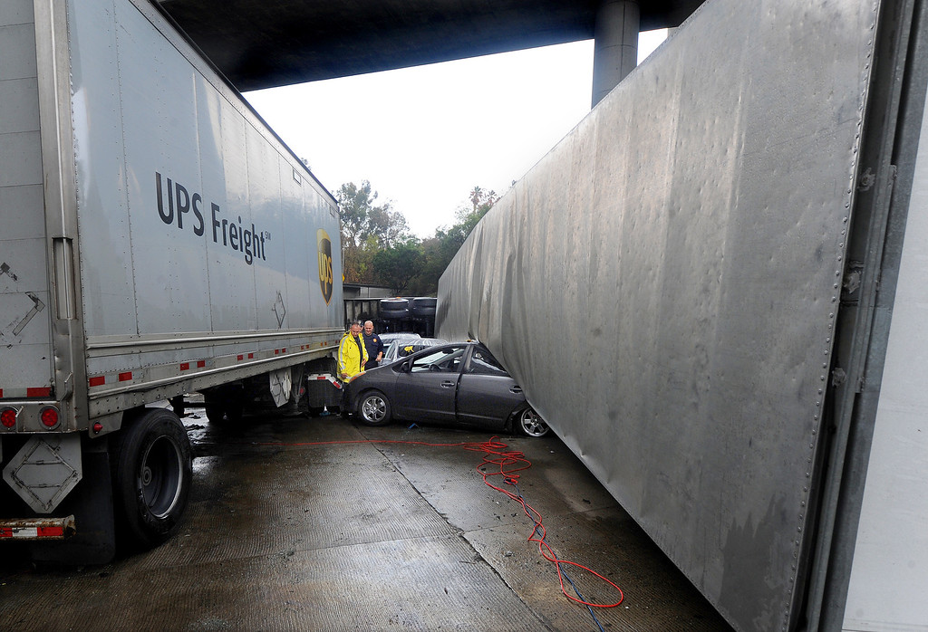 Description of . A Prius car sandwich between two trucks. Three big-rig and two cars crashed, killing a truck driver near the runner on (210) Freeway East.  The accident at 12:01 caused the tunnel to be closed and a SigAlert was called where the tunnel was schedule to reopen by 4 to  5 p.m. Thursday, November 21, 2013. (Photo by Walt Mancini/Pasadena Star-News)