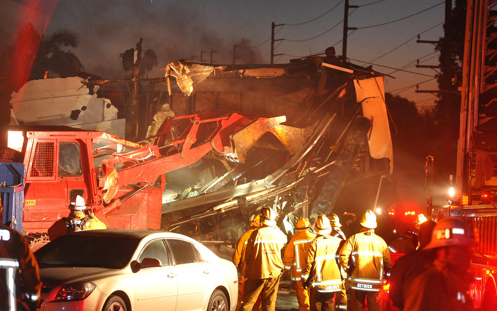 Description of . A Los Angeles County bulldozer knocks down the facade as firefighters wind down fighting an early morning fire at a strip mall on the 15000-block of Leffingwell Road in East Whittier on Tuesday October 1, 2013. Firefighters battled the three-alarm fire that began shortly after 3AM destroying the five-unit strip mall. (San Gabriel Valley Tribune/Staff Photo by Keith Durflinger)