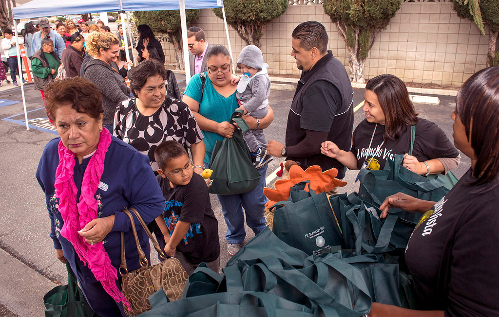 Description of . El Rancho Vista Healthcare Center workers Noe Ramirez and Veronica Guzman, center right, pass out Thanks giving turkeys to some of the 200 families at the Pico Rivera, Calif. facility on Mines Avenue Nov. 21, 2013.  (Staff photo by Leo Jarzomb/Whittier Daily News)