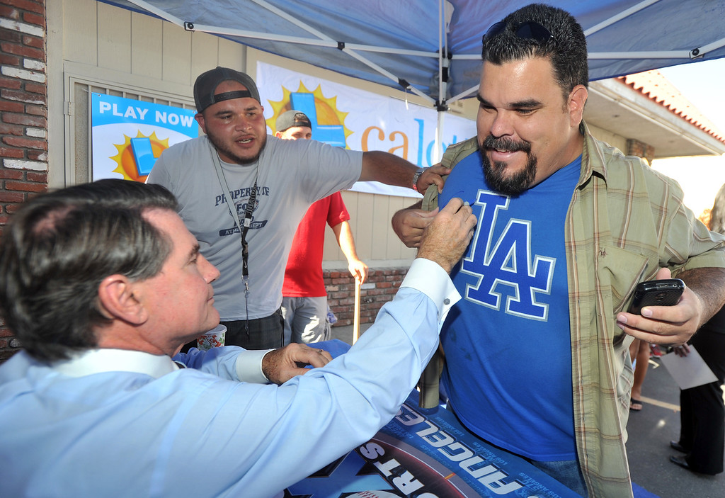 Description of . Former Dodgers first baseman Steve Garvey signs the t-shirt of James Moreno, of Whittier, during a promotion for the California State Lottery's new $5M scratchers at the Barley Bin Liquor Store in Whittier on Wednesday October 2, 2013. Fans lined up around the parking lot to get Garvey's autograph. (Whittier Daily News/Staff Photo by Keith Durflinger)