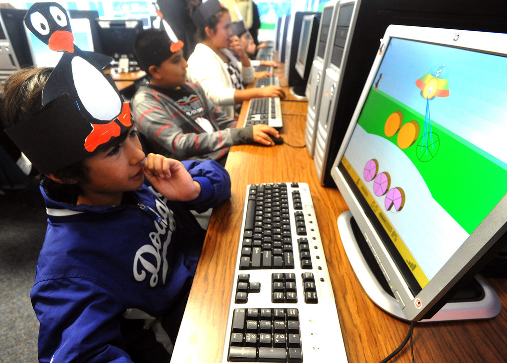 Description of . Fifth-grader Andres Gonzalez works on a math lesson as part of the ST Math Program presented by the Azusa Unified School District and Mind Research Institute at Paramount Elementary School October 28, 2013. Kids wear penquin hats because the mascot for  the new math program is Ji Ji, the penquin. (San Gabriel Valley Tribune/Staff Photo by Keith Durflinger)