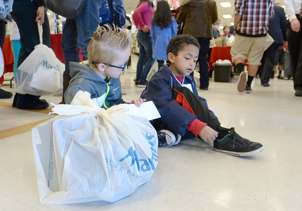 Description of . Sawyer Gartner, 6, and Chris Cooper, 7, make friends during the Rotary Club of La Mirada Christmas Shopping Spree at Marshalls in La Mirada on Wednesday December 11, 2013. Each child is allowed $75 tp spend on clothing and shoes.  (Staff Photo by Keith Durflinger/San Gabriel Valley Tribune)