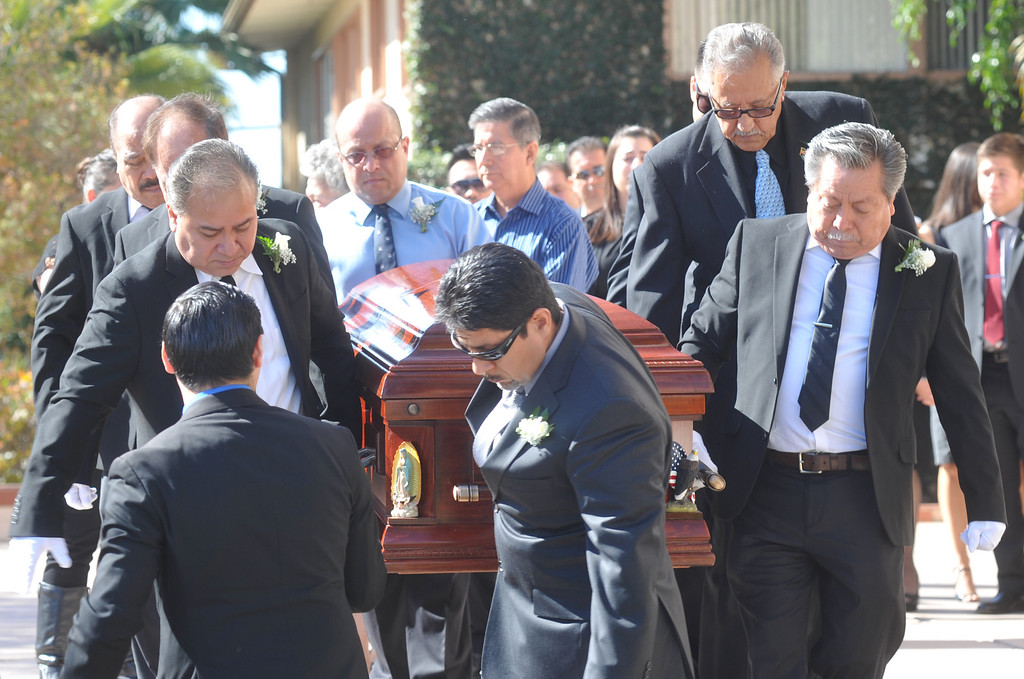 Description of . Pall bearers bring out the casket to the hearse after the funeral service for Mario Jimenez, owner of Mario's Taco's, at St. Hillary's Catholic Church in Pico Rivera on Tuesday October 15, 2013. Jimenez who had been an active member of the community and hosted their free Thanksgiving dinners, died Wednesday October 8th after a long battle with cancer. (Whittier Daily News/Staff Photo by Keith Durflinger)