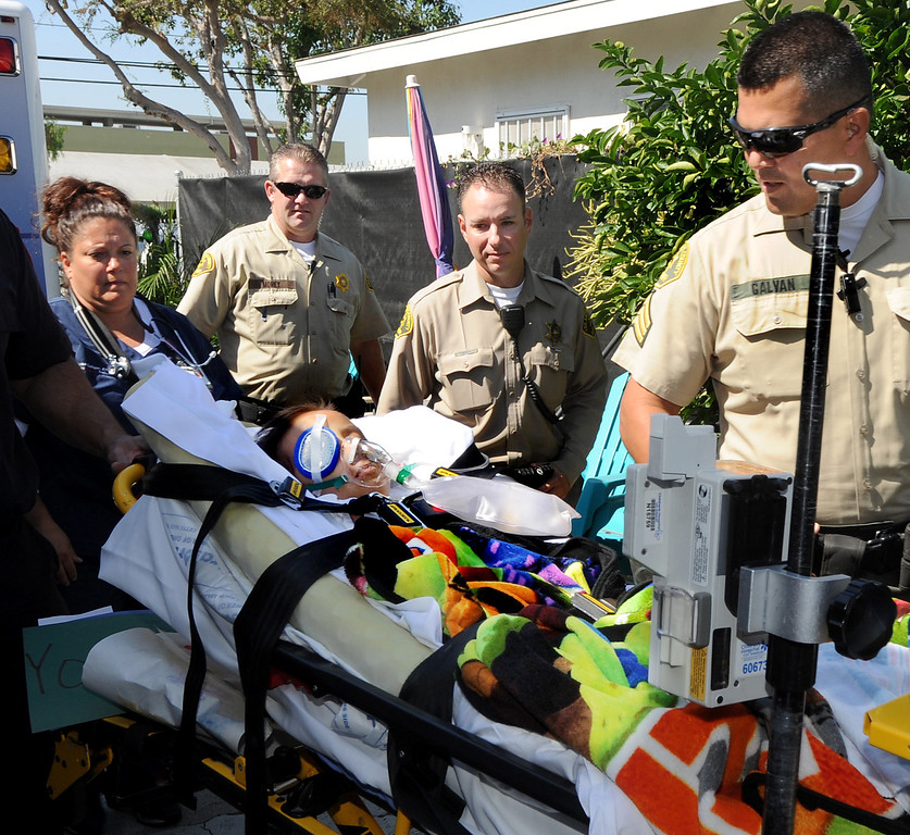 Description of . Los Angeles Sheriff's Deputy Patrick Morey, left, Jason Elkins, and  Sgt. Michael Galvan, escorted Doryan Torres, 6, to his South El Monte home. After nearly a monthlong hospitalization, Doryan Torres was released from Children's Hospital LA  Friday, October 11, 2013, and escorted home by the Sheriff's from the Hollywood hospital. Doryan has been battling Atypical Teratoid Rhabdoid Tumor (ATRT) since he was just 14 months old, a rare condition that produces rapidly reoccurring tumors in the tissues of his central nervous system(Walt Mancini/Pasadena Star-News)