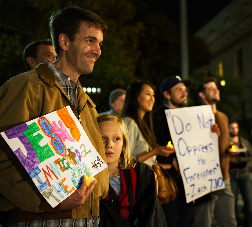 Description of . Matthew Coldwell, adjunct Professor at Fuller and Pastor at Know Presbyterian Church in Pasadena with his daughter Lucy listening to Jennifer Hernandez speak. Fuller Seminary held a march Monday, February 18, 2013, with an estimated 125 people from Fuller Seminary's campus walking to Pasadena City Hall as part of an evangelical community call for immigration reform. The new president Mark Labberton and associate provost Juan Martinez  participated Students song hymns and held signs as they walk on Colorado Boulevard to Pasadena City Hall.(Photo by Walt Mancini/Pasadena Star-News)