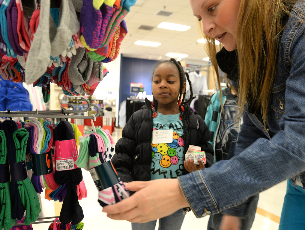 Description of . Volunteer Alicia Millan helps Le'Ann Washington, 6,  choose socks during the Rotary Club of La Mirada Christmas Shopping Spree at Marshalls in La Mirada on Wednesday December 11, 2013. Each child is allowed $75 tp spend on clothing and shoes.  (Staff Photo by Keith Durflinger/San Gabriel Valley Tribune)