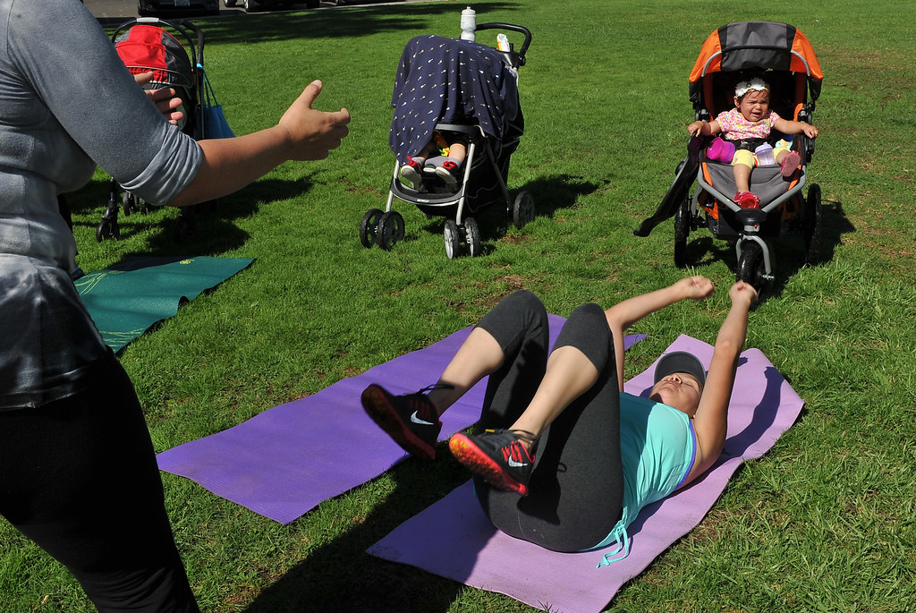 . 9/27/13 - Following a jogging stroller workout, Jessica Andrade of Seal Beach does sit ups.  Long Beach-Stroller Strides gathers moms and their children for fun outdoor exercise at Marine Stadium in Long Beach. For information on classes visit http://longbeach.fit4mom.com/ (Photo by Brittany Murray/Press Telegram)