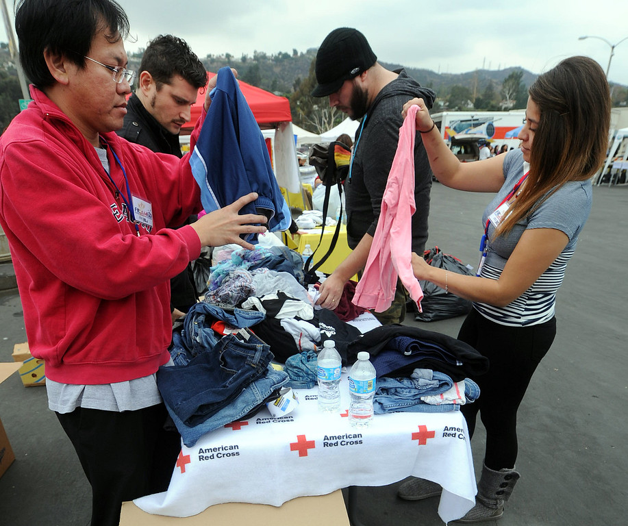 . Lun Sukarna of Rosemead and Jessica Funez of South Gate folding clothes to be boxed and shipped to Philippine Typhoon Relief Donation Drive. PCC along with Vice Mayor Jacque Robinson, the American Red Cross, Filipino American Television, Victory Cargo, and the PNB-Remittance Centers  sponsoring a Philippine Typhoon Relief Donation Drive Donation Drive Drop-Off Rally Wednesday, November 20, 2013 at the Rose Bowl. (Photo by Walt Mancini/Pasadena Star-News)