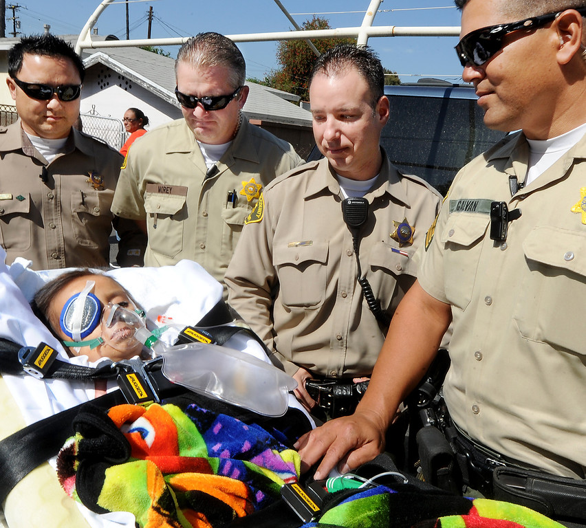 . Los Angeles Deputies Johnny Vo, left, Patrick Morey, Jason Elkins, ans Sgt. Michael Galvan escorted six year old Doryan Torres to his South El Monte home, After nearly a monthlong hospitalization. Doryan Torres was released from Children\'s Hospital LA  Friday, October 11, 2013, and escorted home by the Sheriff\'s from the Hollywood hospital. Doryan has been battling Atypical Teratoid Rhabdoid Tumor (ATRT) since he was just 14 months old, a rare condition that produces rapidly reoccurring tumors in the tissues of his central nervous system(Walt Mancini/Pasadena Star-News)