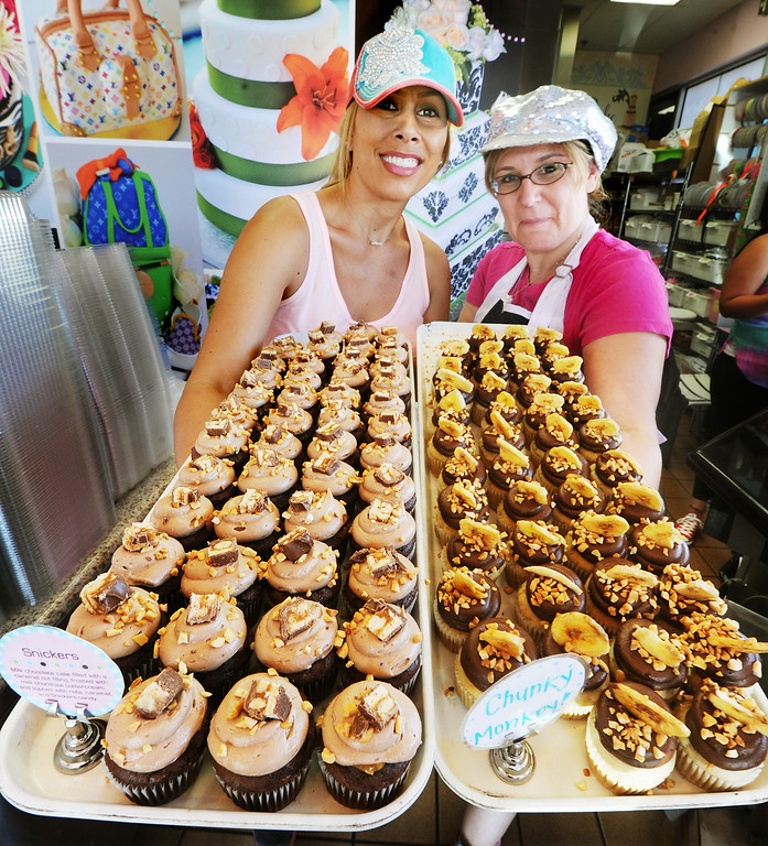 """. Janelle Copeland, owner of The Cake Mamas in Glendora, with Corinne Delgado who has been at  The Cake Mamas from when the business opens holding a \""""Snickers\"""" and \""""Chunky Monkey\"""" tray of cupcakes. The Cake Mamas celebrating its third year in business gave away 1,000 free cupcakes from 10 a.m. to 7:00 p.m. Tuesday, October 1, 2013. The Cake Mamas won the Food Network \""""Cupcake Wars\"""" in 2011.(Photos by Walt Mancini/Pasadena Star-News)"""