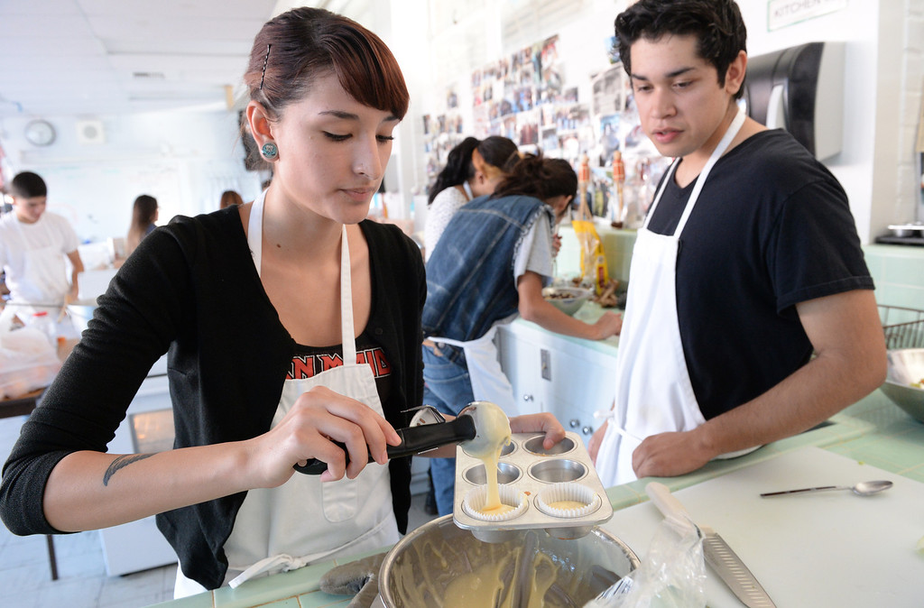 . Olivia Loza and Gustavo Medina make cupcakes as El Rancho High School\'s culinary arts and hospitality class prepare food for the homeless on Wednesday November 27, 2013. The students and volunteers will deliver the food and clothing items in downtown Los Angeles on Thanksgiving. (Whittier Daily News/Staff Photo by Keith Durflinger)