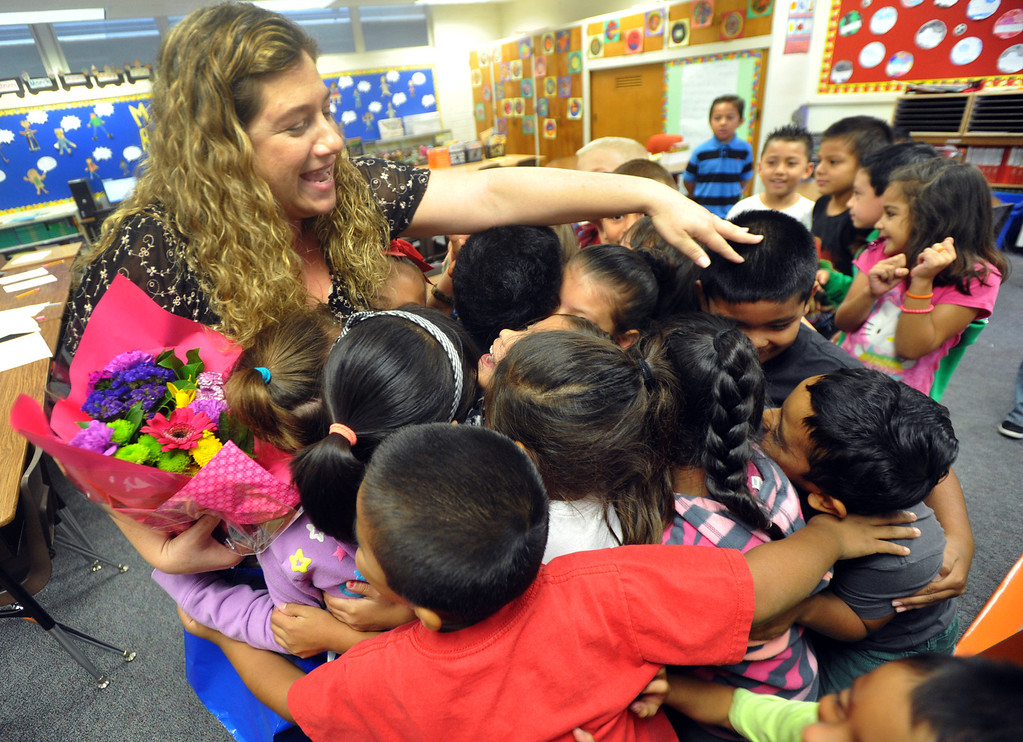 . Second grade teacher Natalia Weberg is presented with flowers and hugs from first grade students after receiving $1,200 worth of classroom supplies and resources from OfficeMax at Ceres Elementary School in Whittier on Wednesday October 2, 2013. Principal Julie Gonzalez nominated the second grade teacher for the Adopt a Classroom grant sponsored by Office Max and Adopt a Classroom. (Whittier Daily News/Staff Photo by Keith Durflinger)