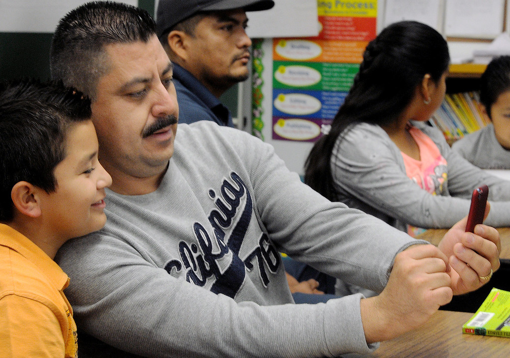 """. Benjamin Huzar, with his dad, Mario Huizar who photographs a cell phone picture of them in class at Elwin Elementary School in Baldwin Park. Elwin Elementary hosted, \""""Bring Your Dad to School\"""" Day Wednesday, October 2, 2013.(Walt Mancini/San Gabriel Valley Tribune)"""