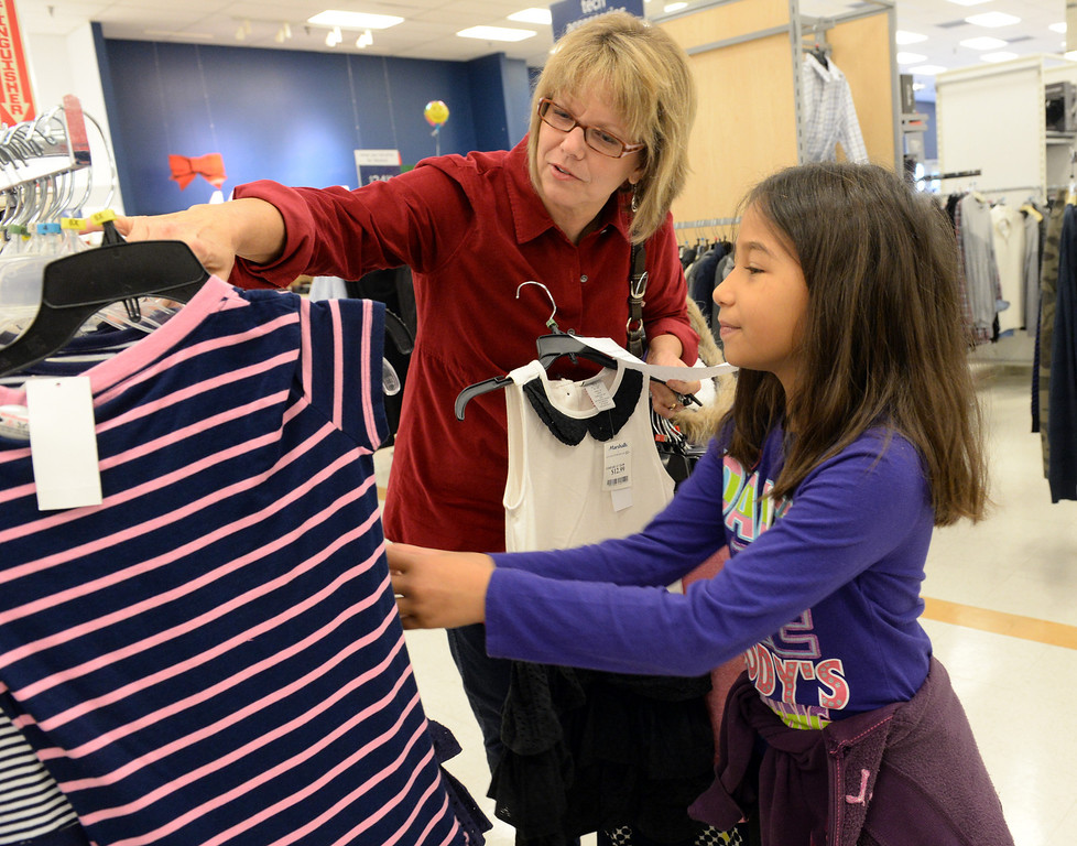 . Janis Jones helps Andrea Arguello, 9, shop for clothing during the Rotary Club of La Mirada Christmas Shopping Spree at Marshalls in La Mirada on Wednesday December 11, 2013. Each child is allowed $75 tp spend on clothing and shoes.  (Staff Photo by Keith Durflinger/San Gabriel Valley Tribune)