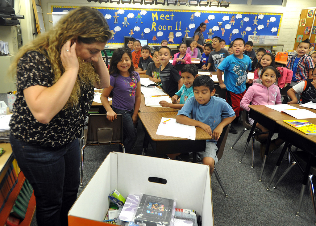 . OfficeMax representatives surprise second grade teacher Natalia Weberg with $1,200 worth of classroom supplies and resources at Ceres Elementary School in Whittier on Wednesday October 2, 2013. Principal Julie Gonzalez nominated the second grade teacher for the Adopt a Classroom grant sponsored by Office Max and Adopt a Classroom. (Whittier Daily News/Staff Photo by Keith Durflinger)