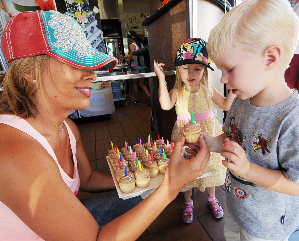 """. Janelle Copeland, owner of The Cake Mamas in Glendora, giving free cupcake to twins, Shannon and Patrick Conrad of Glendora.  The Cake Mamas, celebrated their birthday by giving  1,000 free cupcakes from 10 a.m. to 7:00 p.m. Tuesday, October 1, 2013. The Cake Mamas won the Food Network \""""Cupcake Wars\"""" in 2011.(Photos by Walt Mancini/Pasadena Star-News)"""