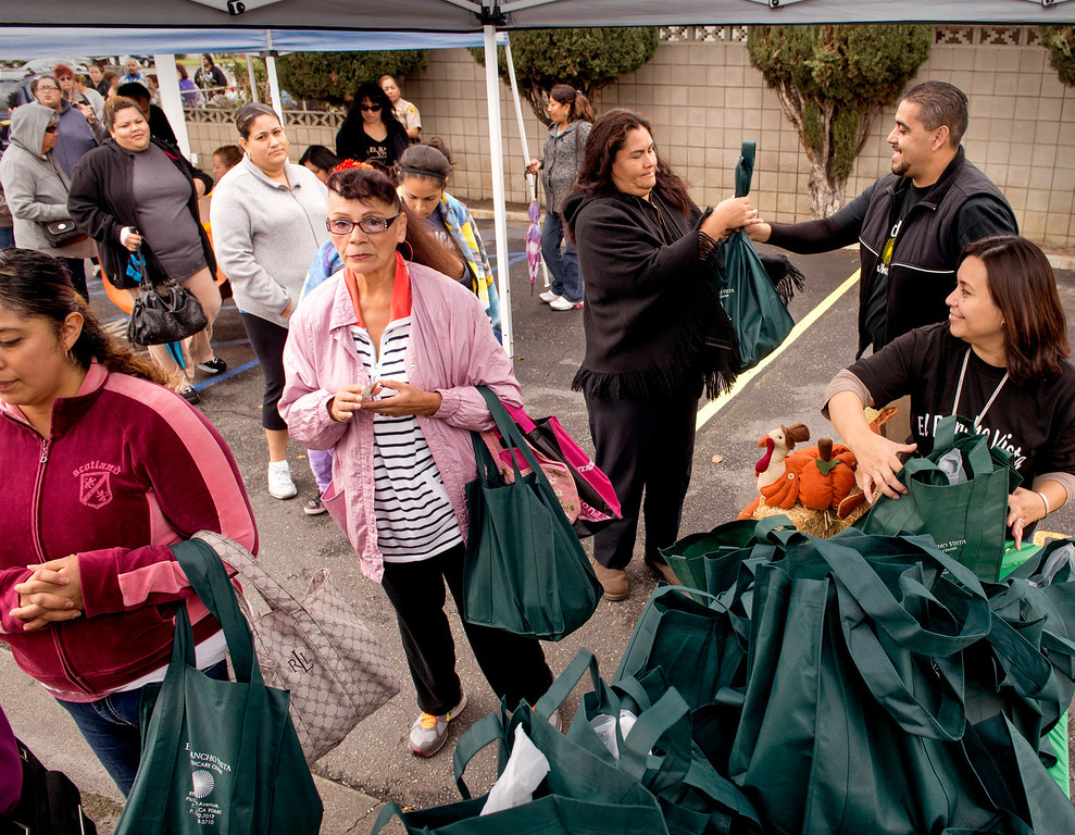 . El Rancho Vista Healthcare Center workers pass out Thanksgiving turkeys to 200 needy families at the Pico Rivera, Calif. facility on Mines Avenue Nov. 21, 2013.  (Staff photo by Leo Jarzomb/Whittier Daily News)