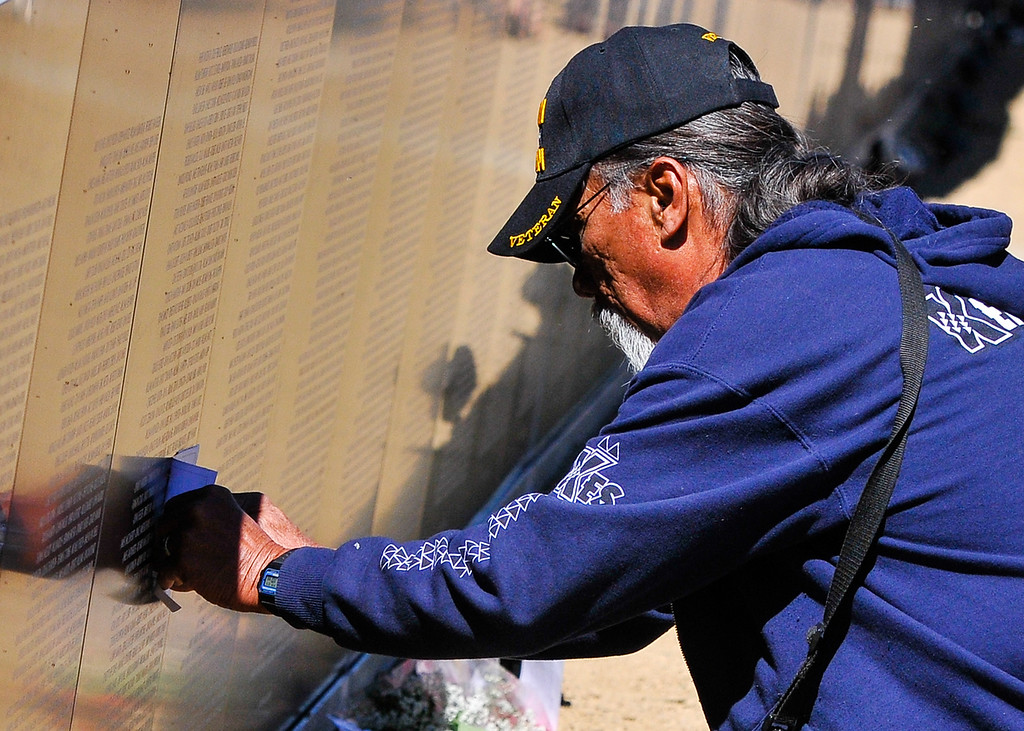 """. Vietnam veteran Frank Paulo Jr., of Big Bear, makes an impression rubbing of the name of a loved-one written the Traveling Vietnam Wall replica memorial at Meadow Park in Big Bear Lake on Friday, Sept. 27, 2013. \""""It\'s so hard to be (at the memorial) knowing you made it home, and seeing that they didn\'t,\"""" Paulo said as he held back tears. (Photo by Rachel Luna / San Bernardino Sun)"""