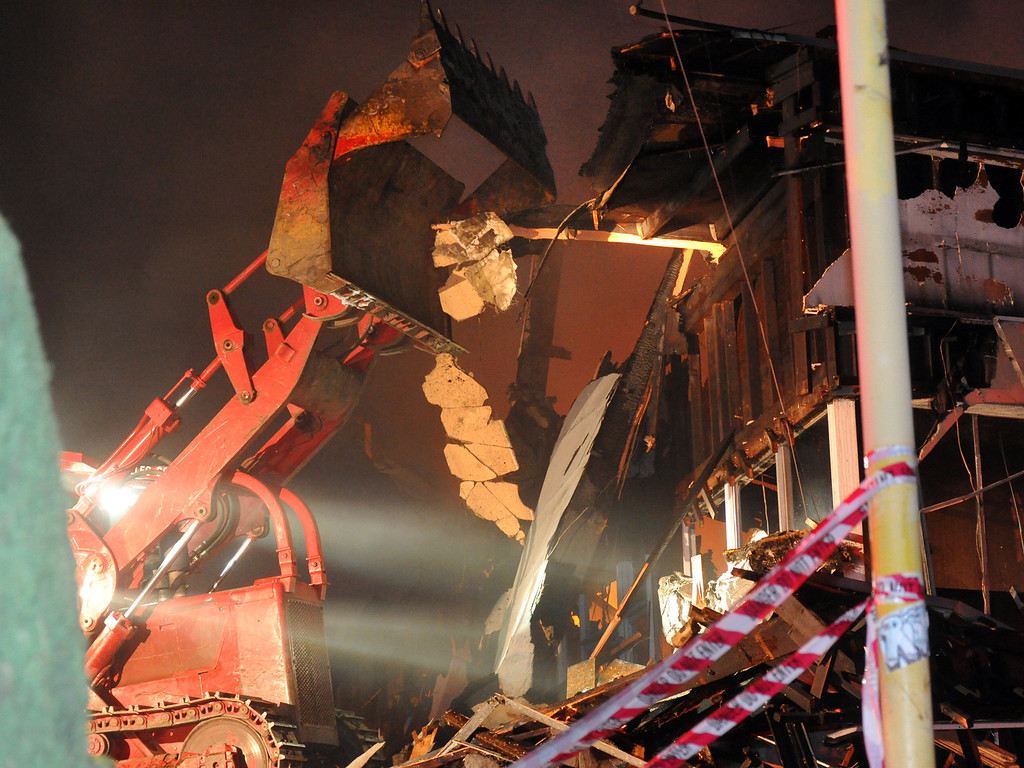 . A Los Angeles County bulldozer knocks down the facade as firefighters wind down fighting an early morning fire at a strip mall on the 15000-block of Leffingwell Road in East Whittier on Tuesday October 1, 2013. Firefighters battled the three-alarm fire that began shortly after 3AM destroying the five-unit strip mall. (San Gabriel Valley Tribune/Staff Photo by Keith Durflinger)