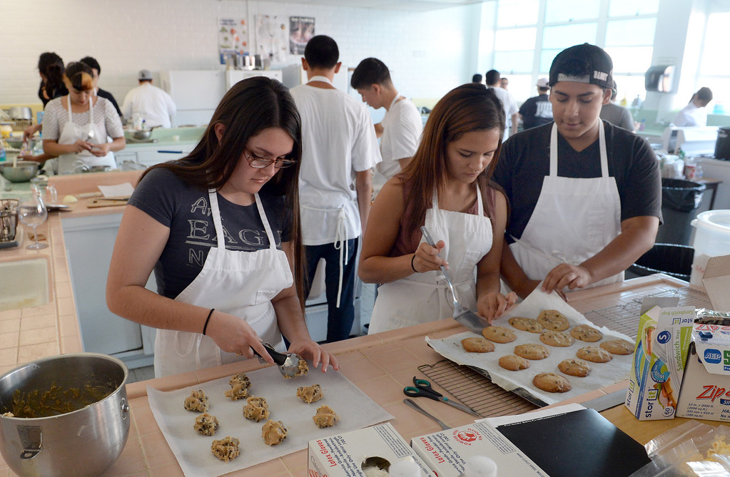 . Students, from left, Samantha Aragon, 17, Destiny Avina, 16, and Daniel Plancarte, 14, make chocolate chip cookies as El Rancho High School\'s culinary arts and hospitality class prepare food for the homeless on Wednesday November 27, 2013. The students and volunteers will deliver the food and clothing items in downtown Los Angeles on Thanksgiving. (Whittier Daily News/Staff Photo by Keith Durflinger)