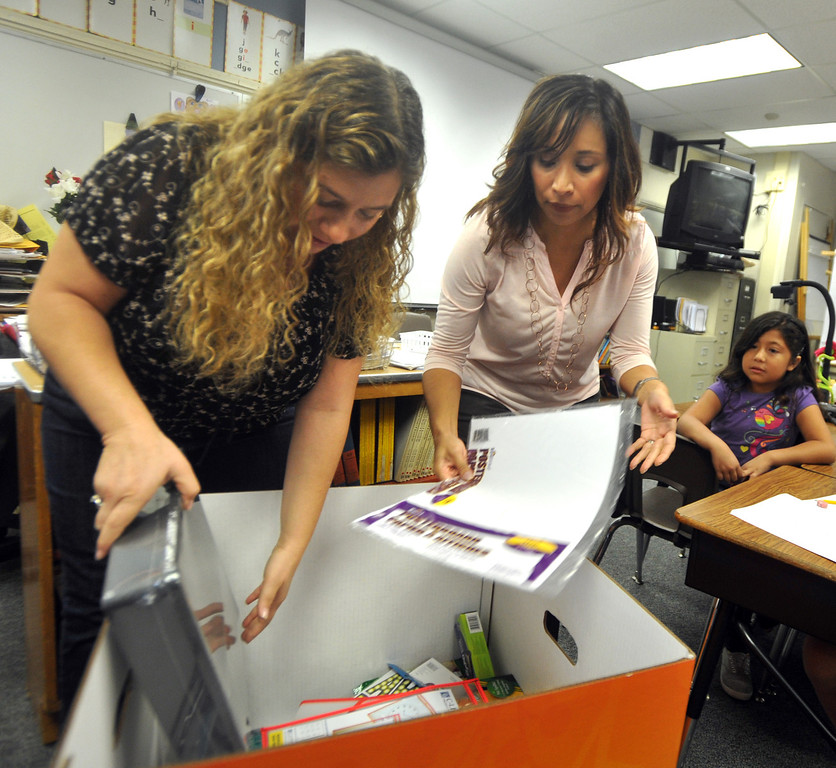 . Second grade teacher Natalia Weberg, left, and Principal Julie Gonzalez look through a box filled with $1,200 worth of classroom supplies and resources after being surprised by OfficeMax representatives at Ceres Elementary School in Whittier on Wednesday October 2, 2013. Principal Julie Gonzalez nominated the second grade teacher for the Adopt a Classroom grant sponsored by Office Max and Adopt a Classroom. (Whittier Daily News/Staff Photo by Keith Durflinger)