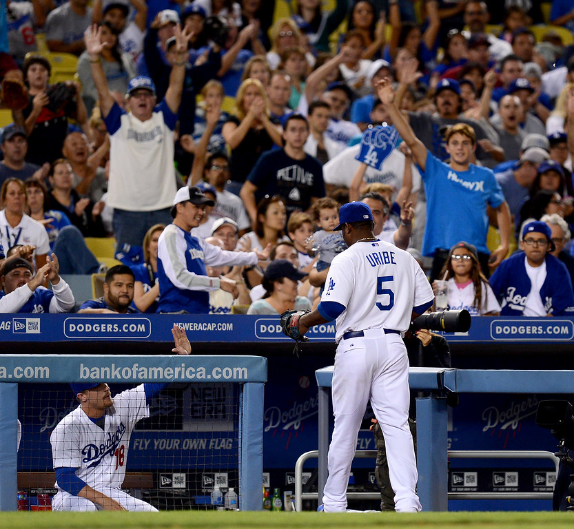 . The crowd celebrates as Dodgers\' Juan Uribe #5 makes a an out at third as they play the Rockies at Dodger Stadium Saturday, September 28, 2013. The bat went into the crowd. (Photo by Sarah Reingewirtz/Pasadena Star-News)