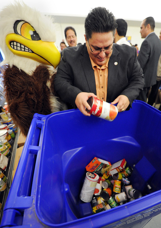 ". Board of Education President, Hector Chacon placing food in container to help start ""War On Hunger\"", food drive.The Montebello Unified School District and its partners bringing the community together to assist local families in need through its 5th Annual War on Hunger Food Drive.  the District\'s Kick-Off Event was held at Montebello Intermediate School Wednesday, October 16, 21013. (Photos by Walt Mancini/Pasadena Star-News)"