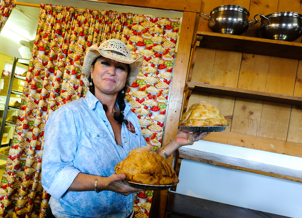. Waitress Kris Turner smiles as she delivers two Apple Annie\'s Bakery & Restaurant\'s famous five-pound apple pies to a customer at Apple Annie\'s in Oak Glen on Thursday, Sept. 27, 2013. Apple Annie\'s sells 400 apple pies each week day, and more than 1,000 pies on Saturdays and Sundays. (Photo by Rachel Luna / San Bernardino Sun)